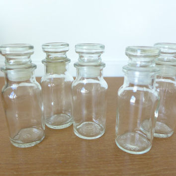 Five glass spice or apothecary jars with stoppers, different styles and sizes