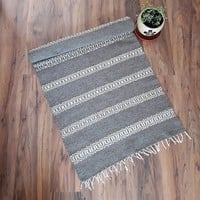Stylish grey handwoven wool rug with of white stripes for your home decor by the weaving team of Rugs N' Bags