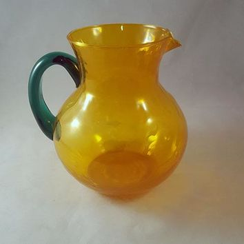 Hand Blown Globe Shaped Orange Glass Pitcher with Green Handle