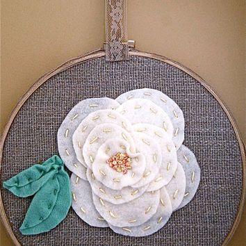 6 inch round embroidered wall hanging with hand stitched flower.
