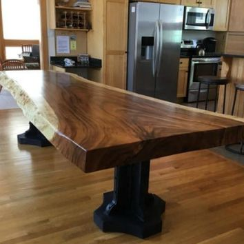 Live edge dining table with a hand crafted custom pedestal base