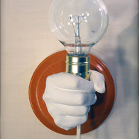 Hand Holding Bulb Wall Lamp Orange by KaraGunter