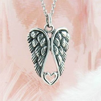 Pair of Angel Wings Cradling a Heart Necklace in Sterling Silver