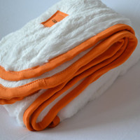 Double plush baby blanket. Blanket size: Size 31 by 40 inches. Colors- White with orange edging.