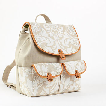 Beige fabric backpack. Rucksack  with floral print flap and orange leather edges.