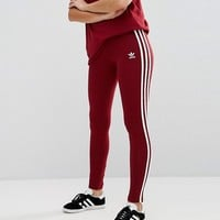 adidas Originals Three Stripe Legging In Burgundy at asos.com