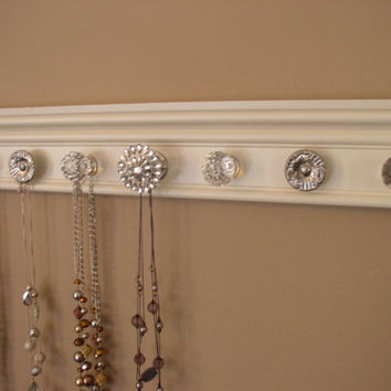 jewelry holder This wall necklace organizer has 7 decorative cabinet knobs featuring large rhinestone center on off white background 20*