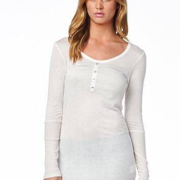 Simple and super soft henley top featuring textured fabrication, a round neckline, long sleeves, slightly sheer triblended fabrication, faux button up at the front, and tunic length construction.