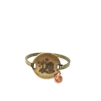 We would love to tell you a little bit about Top Shelf brand jewelry line so you may appreciate the wonderful handcrafted Engraved Mermaid vintage brass locker tag cuff with a dainty copper color penny you are looking at! This is a costume jewelry manufact