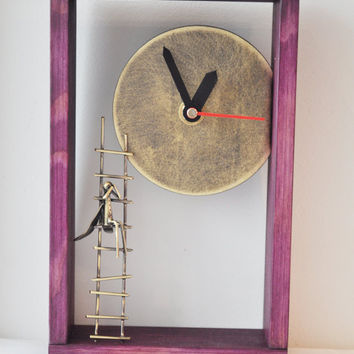 Bronze angel clock in a wooden purple frame, miniature sculpture of angel on a ladder under sun disk/clock