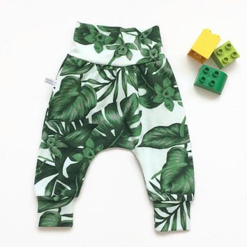 Baby harem pants with monstera leaves. Off white pants with same fabric waistband and cuffs. Comfortable toddler pants. Jersey knit fabric.