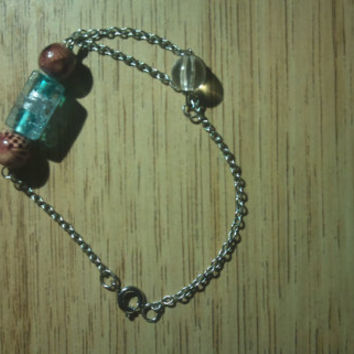 Bracelet made of chain with wood, glass and plastic beads