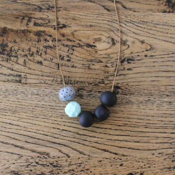 No. 12- Handmade polymer clay beads featuring black, geometric pastel mint and perforated grey on light brown waxed cord.