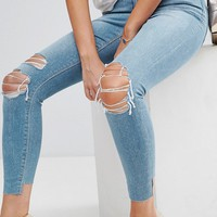 ASOS PETITE RIDLEY High Waist Skinny Jeans in Albie Lightwash Blue with Rips and Reverse Stepped Hems at asos.com