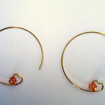 Minimalist gold tone hoop earrings with heart and swarovski crystals.