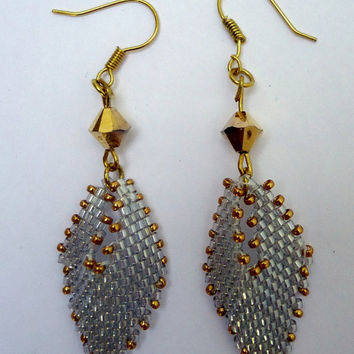 Beaded earrings with silver delicas edged with gold seed beads hanging from gold swarovski crystals and gold tone hypo allergenic ear wires.