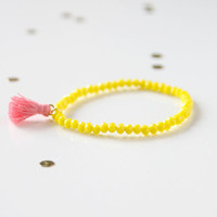 Yellow bracelet with pink tassel