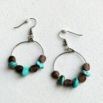 Turquoise bead and copper colored beaded circular earrings.