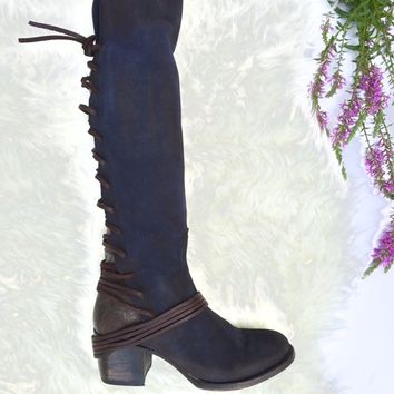 These fashionable knee high boots feature a soft hand distressed finish suede at front, contrast with grey leather back adjustable lace up at shaft for custom fit, wrap around at ankle, low stack heel, round toe, and a drawstring collar that ties at the ba