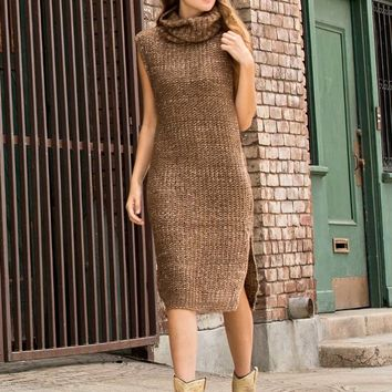 This fashionable sweater dress features a soft chunky knit fabrication, turtleneck, sleeveless, and finish with symmetrical and slit at left side of bottom hemline. Unlined. Pair with Freebird by Steven Coal Boots and leatherette leggings and floppy hat.