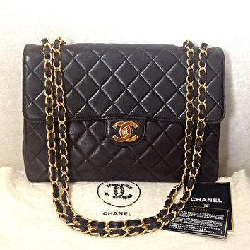 Vintage CHANEL black lamb leather large, jumbo shoulder bag with a golden CC closure and chain strap. 2.55 classic purse
