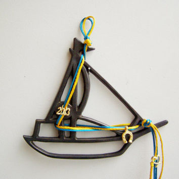 Metal sailboat wallhanging,  oxidised brass sculpture of a Greek sailboat, brass outline of a boat with satin cords and charms