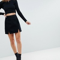 ASOS DESIGN denim mini skirt in washed black with split detail at asos.com