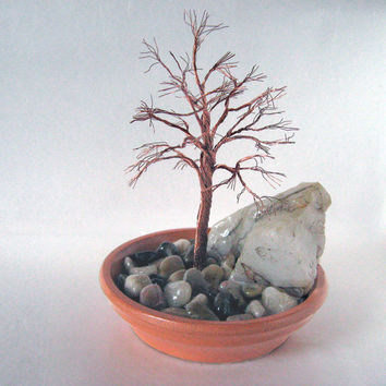 A zen garden in a terra-cotta plate - copper, quartz and river rock combine for a natural, peaceful feeling.