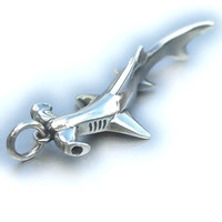 Silver hammerhead shark pendant set with natural blue sapphires for its eyes.