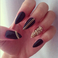 Black stiletto nails with gold chains and gold ring finger