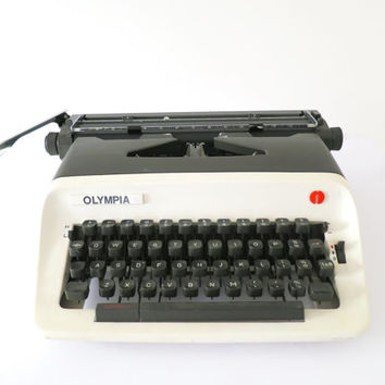 Black & White A3 Olympia Working Typewriter. In Good Condition. Includes Plastic Carry Protective Case.