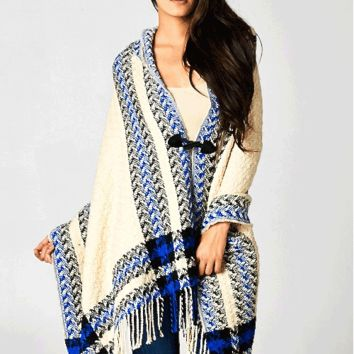 This cozy open long sleeve knit cape style sweater has a fringe hem with black color leatherette toggle closure front, asymmetrical front, black/vanilla/blue mixed plaid pattern print throughout and finish hooded design. Pair with skinny jeans and fringe b