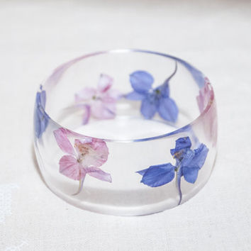 Wide bracelet transparent epoxy jewelry resin with purple and pink dried flowers.