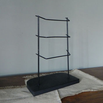 Vintage black metal display rack with three rods on wooden base