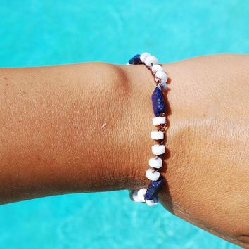 Boho crocheted bracelet made with blue lazuri lapis beads and white shell beads clasped together with a vintage lucite button and tassel