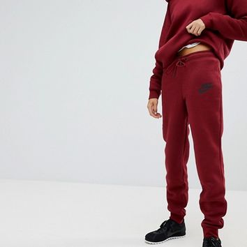 Nike Rally Tight Fit Sweat Pants In Burgundy at asos.com