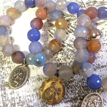Sky Blue stretchy Bracelet with your choice of  Religious Medal.  Most are Antique medals.