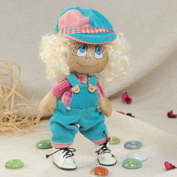 Handmade small funny soft doll in blue jumping suit with white curly hair