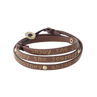 "Brown leather wrap bracelet with gold tone studs stamped ""Enjoy the journey""."