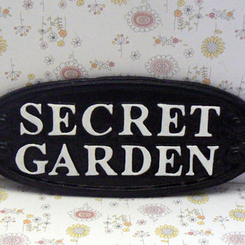 Secret Garden Gate Patio Wall Plaque Sign Cast Iron Glam Black Raised Letters Bright White Oval Oblong Ornate Scroll Accented Wall Door Sign