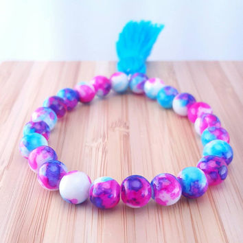 Bright and colorful beaded tassel bracelet // violet, fuschia, and blur splattered beads // bright blue silk-like tassel // boho bracelet