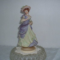 La Mademoiselle Music Box, turns on her pedestal as the music plays.  Soft colors of lilac and sage