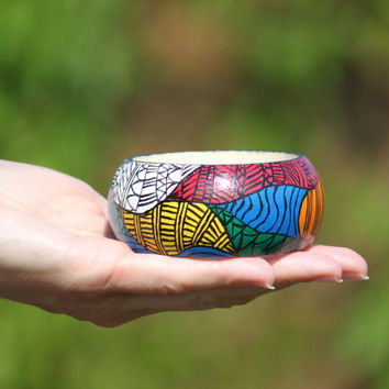 Hand-painted colourful wooden bracelet with black aztec pattern. Handpainted bangle