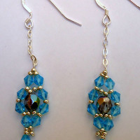 Beaded earrings in a flower pattern with blue bicone crystals, Miyuki seed beads and fire mountain gems with sterling chain and ear wires.
