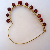 Gold tone open heart earrings with garnets wrapped around one side. Handmade