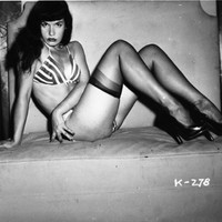 Bettie Page Reclining on Chair in Striped Bikini 8x10 Inch Photograph