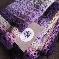 A Crochet Baby Blanket made out of wool yarn in purple, violet, gray colors