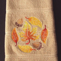 Fall - Thanksgiving Kitchen dish towel with embroidered fall colored leaves of yellow, orange and red and acorns.