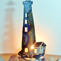 Lighthouse, torched metal to create the bluish colors. A choice of light bulb colors creates multiple color reflections