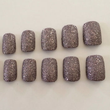 A set of 20 textured, light pink/purple nails in 10 different sizes